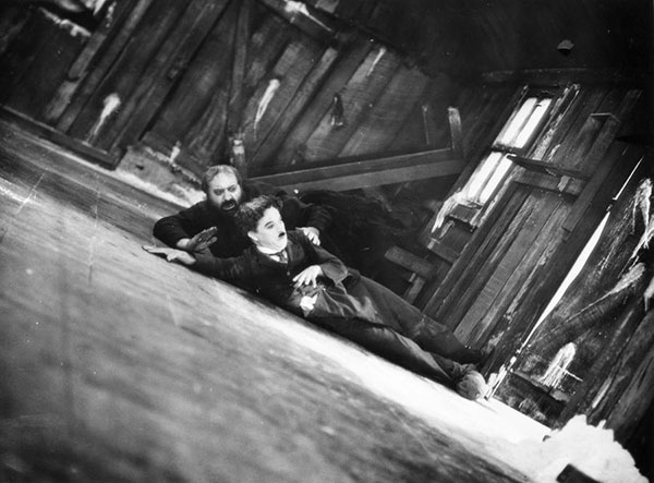 Charlie Chaplin and Mack Swain struggle with a teetering house in The Gold Rush (1924).